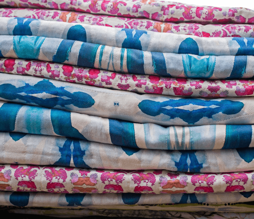 Stack of pink and blue patterned luxury organic quilted coverlets