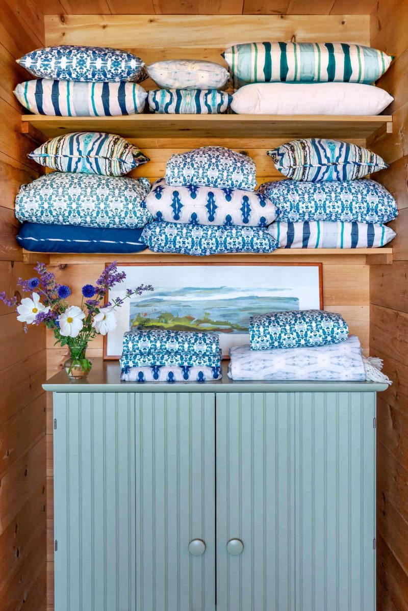 Cedar shelves filled with blue patterned organic bedding and pillows above a mineral blue cabinet