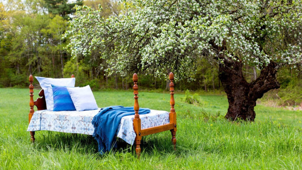 Antique bed in a field with organic cotton textiles