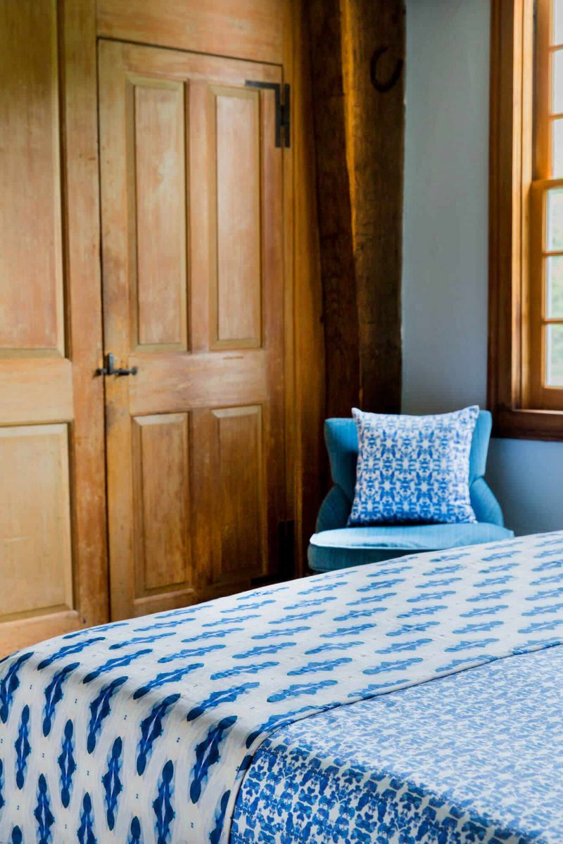 Wooden closet and blue organic pillow behind the corner of a bed with blue organic bedding and coverlet