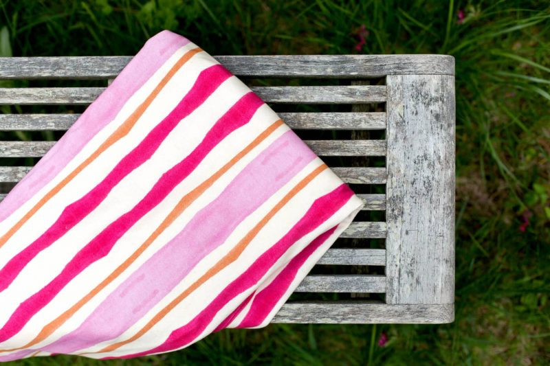 Pink watercolor stripe patterned blanket folded outdoors on a rustic wood bench