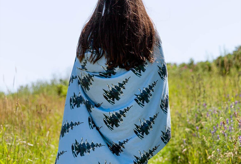 Brunette woman wrapped in a pine tree patterned blanket walking in a field
