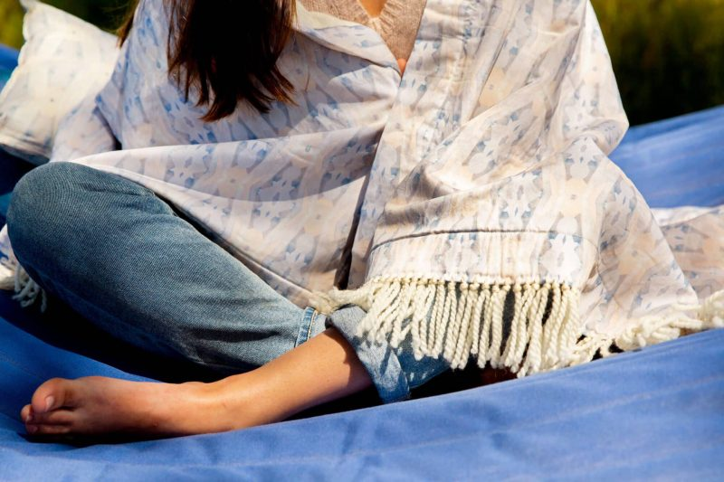 Barefoot woman wearing jeans torso wrapped in an organic fringed blanket