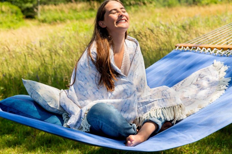 Brunette woman wrapped in an organic light blue blanket smiling into the sunlight while sitting corsslegged on a blue hammock