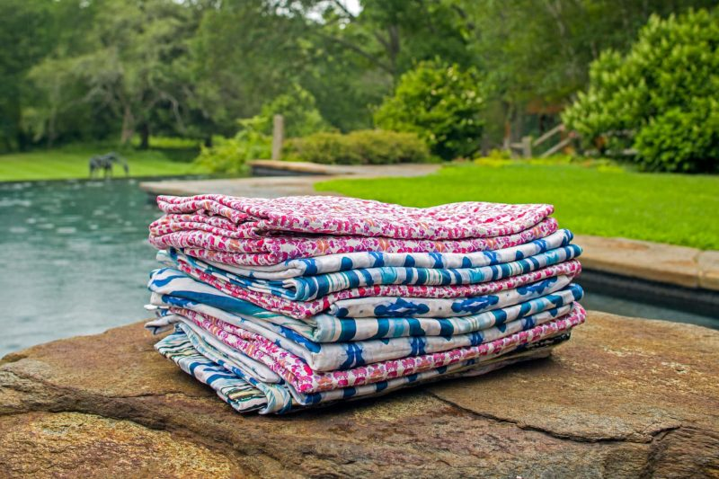 Stack of luxury organic pink and blue quilts on a rock outdoors