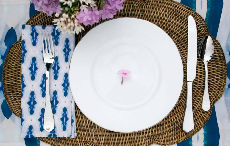 White plate with single pink flower on a wicker placemat with silverware and organic diamond patterned napkin