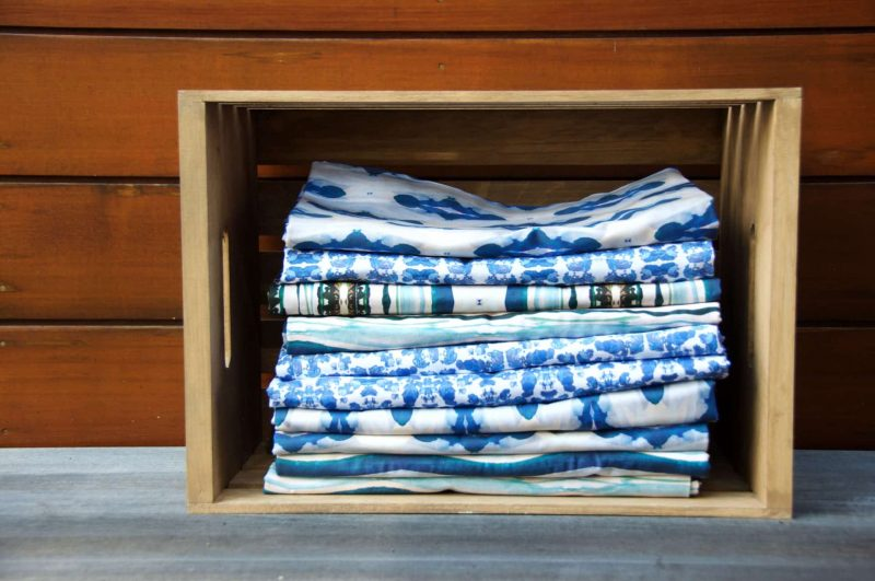 Stack of folded luxury organic tablecloths outside in a rustic wooden crate