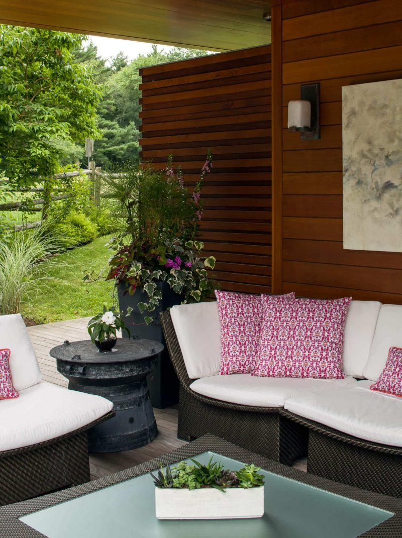 Outdoor living room with couch and pink organic throw pillows