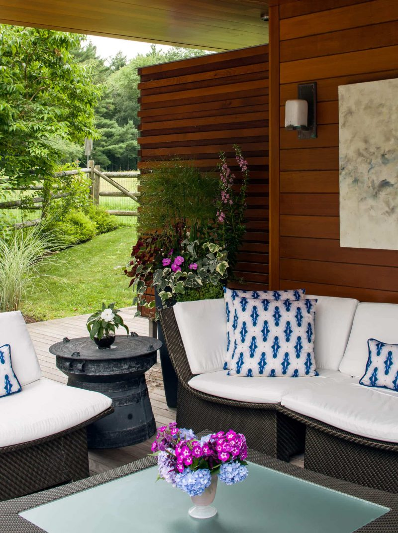 Outdoor living room with blue diamond patterned organic pillows and pink flower arrangements
