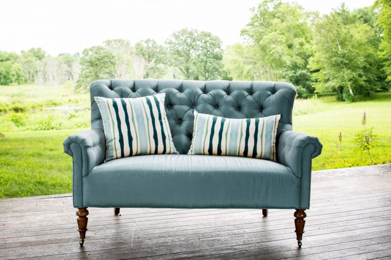 Two green organic watercolor striped pillows placed outdoors on a light blue sette