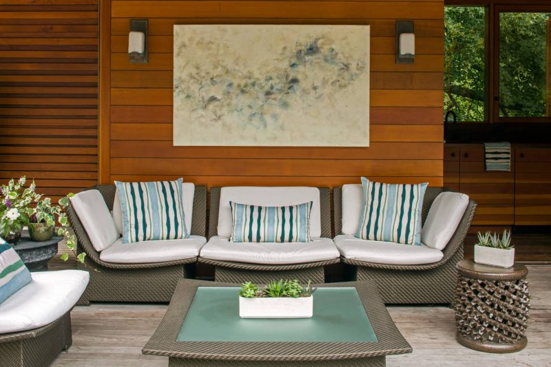 outdoor living room with couch coffee table and organic green watercolor stripe patterned pillows