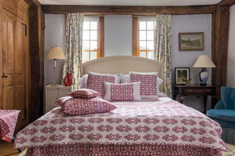 Pink organic coverlet and throw pillows on a bed in a light blue bedroom