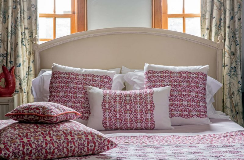 organic pink lace patterned pillows on a bed