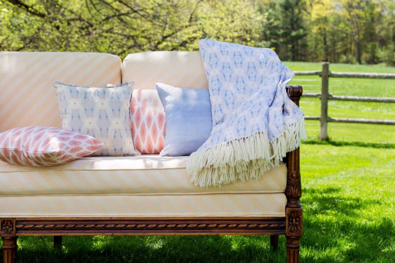 Periwinkle and orange organic pillows and blanket outdoors on a peach sette