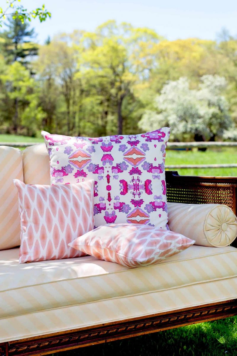 Pink and orange tribal patterned pillow and two small orange diamond patterned pillows on a peach sette outdoors