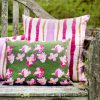 Two pink striped organic pillows and a green floral pillow on a rustic bench in a garden