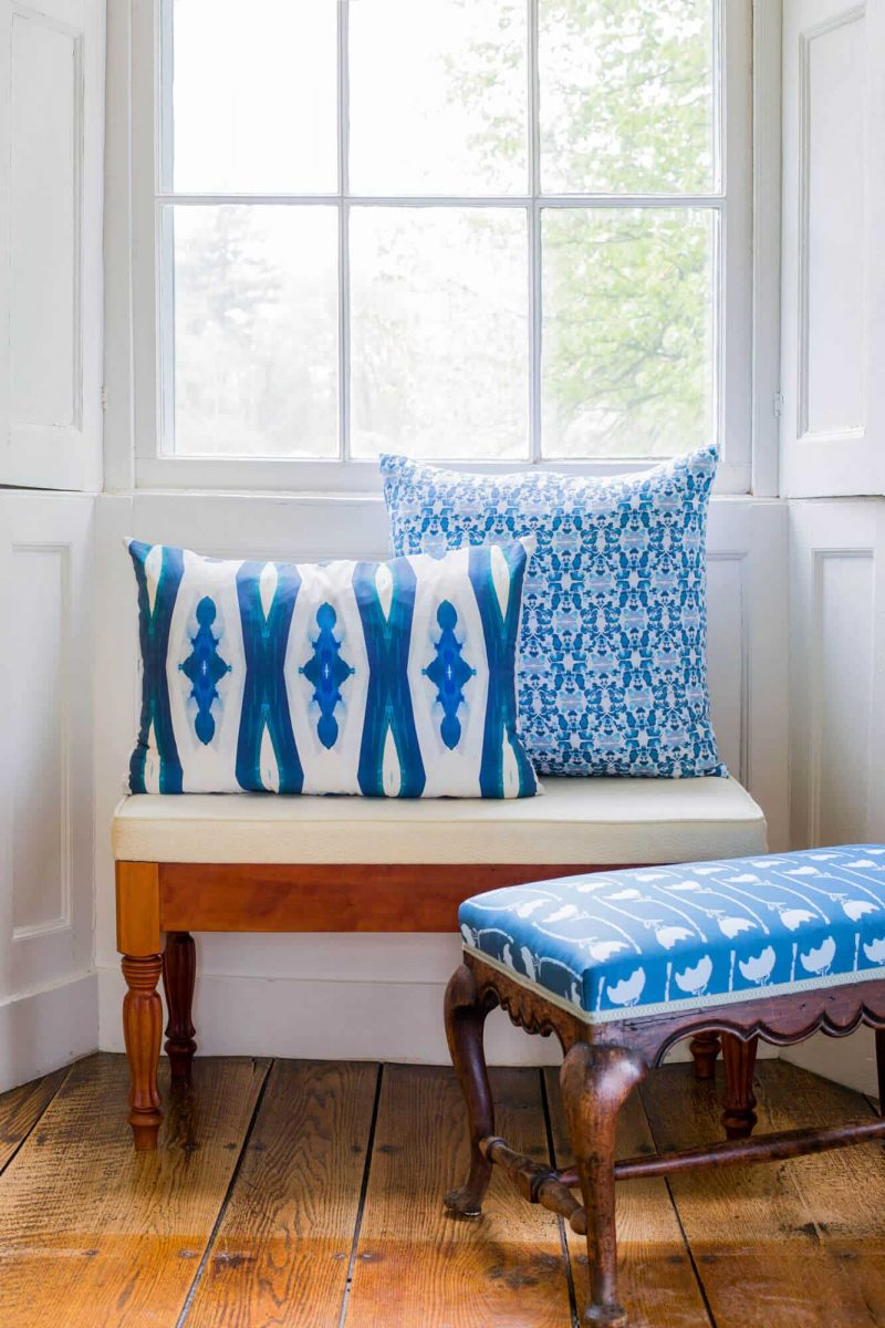 Two organic blue pillows and two upholstered benches in front of a white window