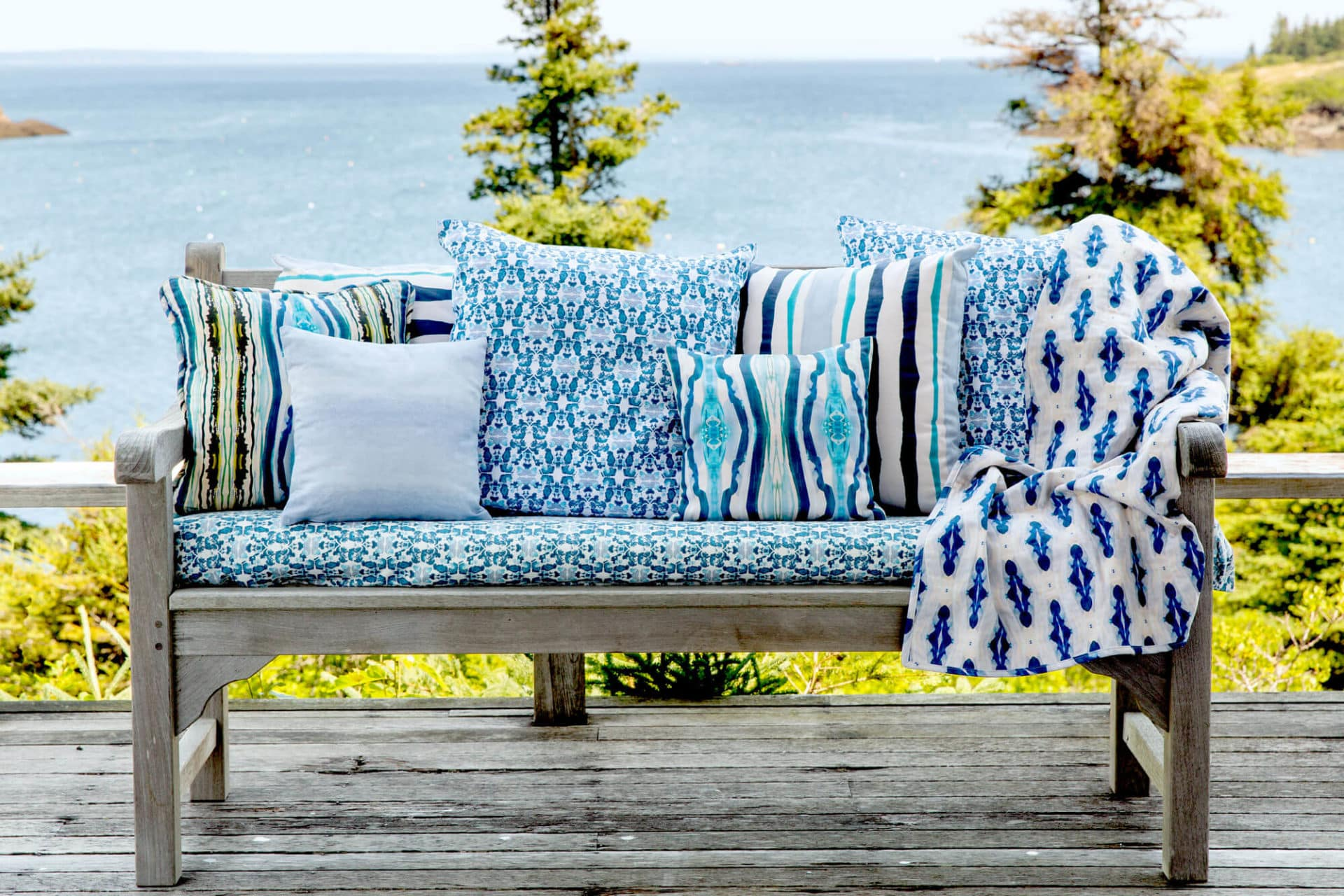 Organic blue pillows and blanket displayed on a rustic bench in front of the ocean