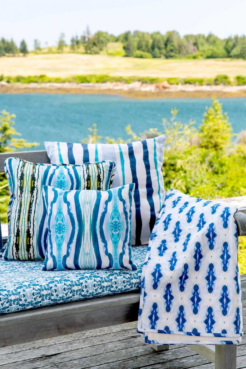 Three organic blue pillows and a blanket on a rustic bench with a view of the maine ocean