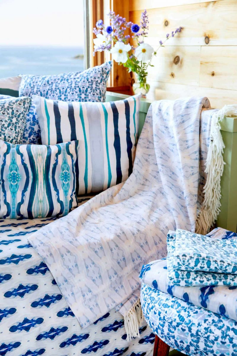 Blue organic pillows and blankets stacked in front of a window with an ocean view
