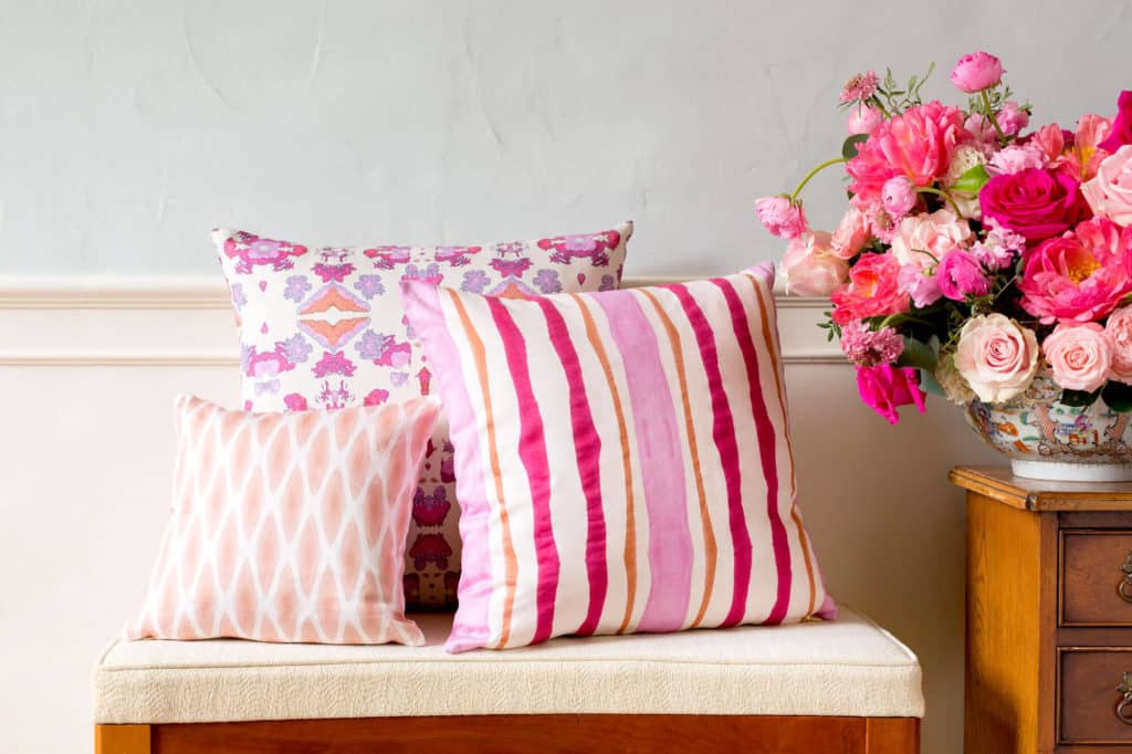 Three pink and orange organic pillows on a bench next to a pink floral arrangement