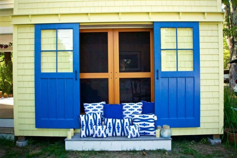 Organic blue diamond patterned pillows sitting on the steps of a yellow barn with bright blue doors