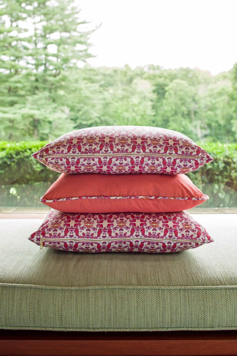 Two pink patterned pillows and one coral pillow vertically stacked on a green bench