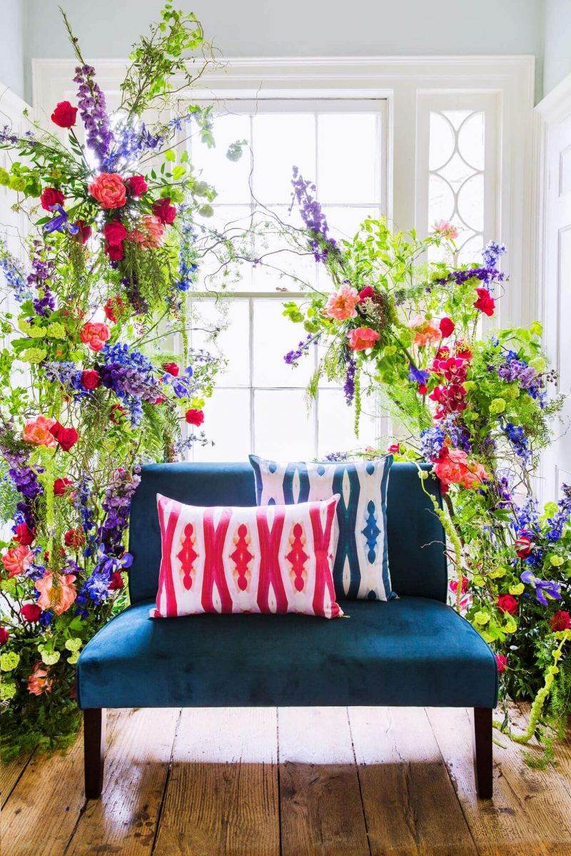 Two diamond patterned organic pillows on a teal sette surrounded by colorful flowers