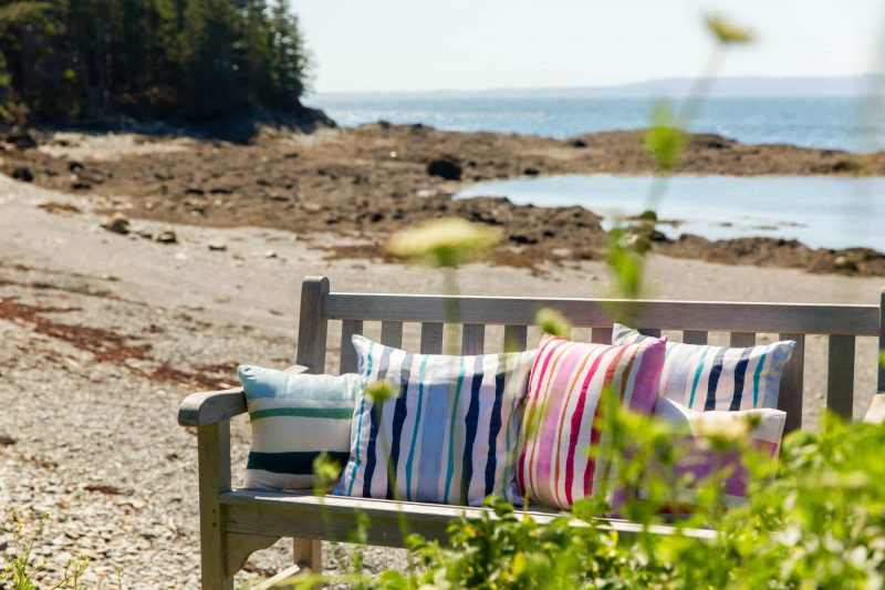 Rustic bench on a Maine beach covered in blue pink and orange organic pillows
