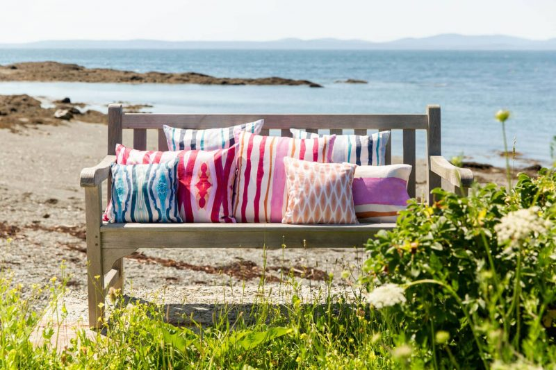 Rustic bench on the beach covered in blue pink and orange organic pillows
