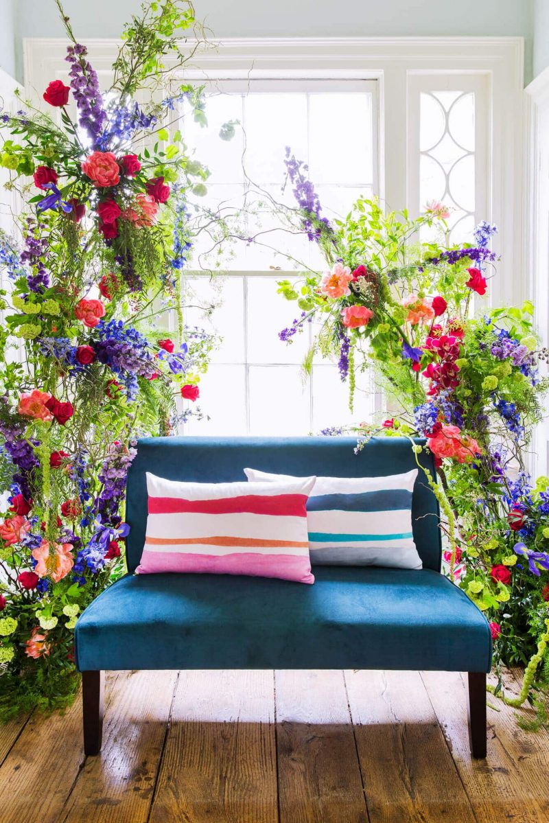 Two watercolor stripe organic pillows on a teal sette surrounded by colorful flowers
