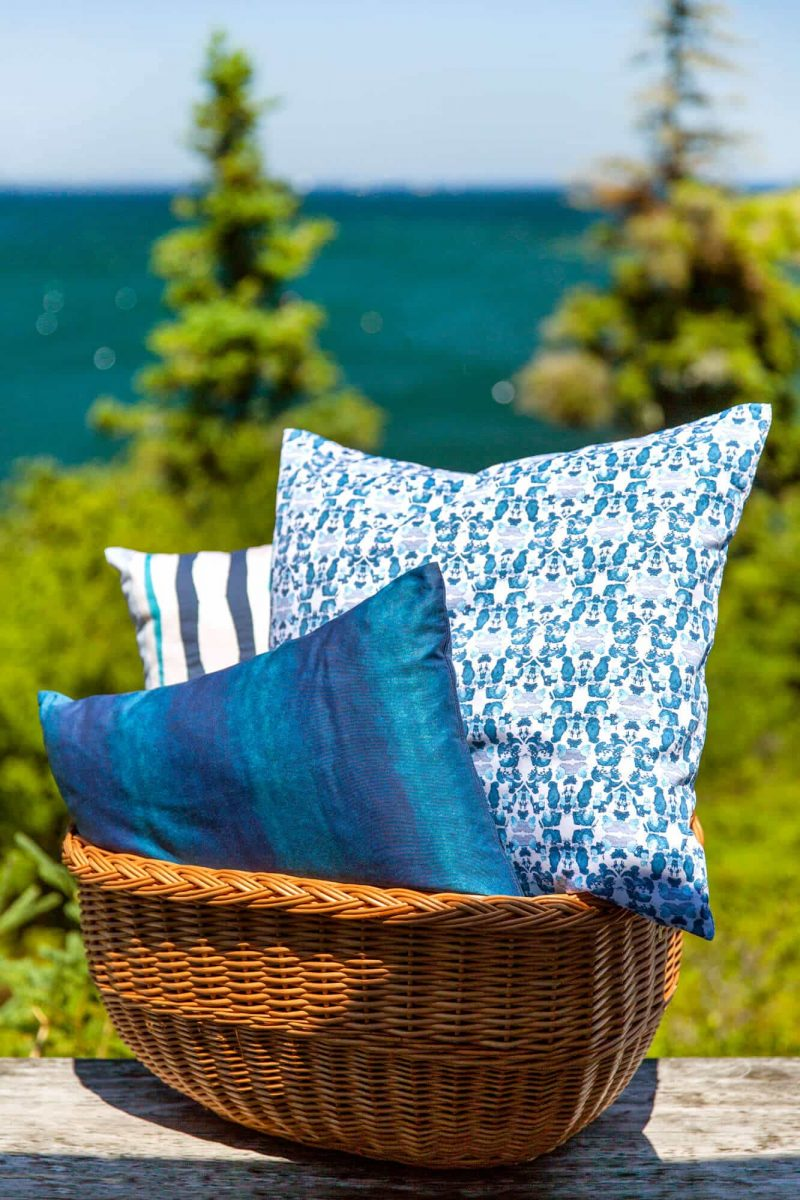 Three blue pillows in a brown basket in front of the ocean