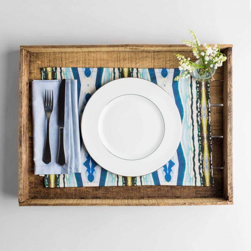 Luxury organic abstract watercolor stripe placemat place setting with a white plate and white flowers in a vase