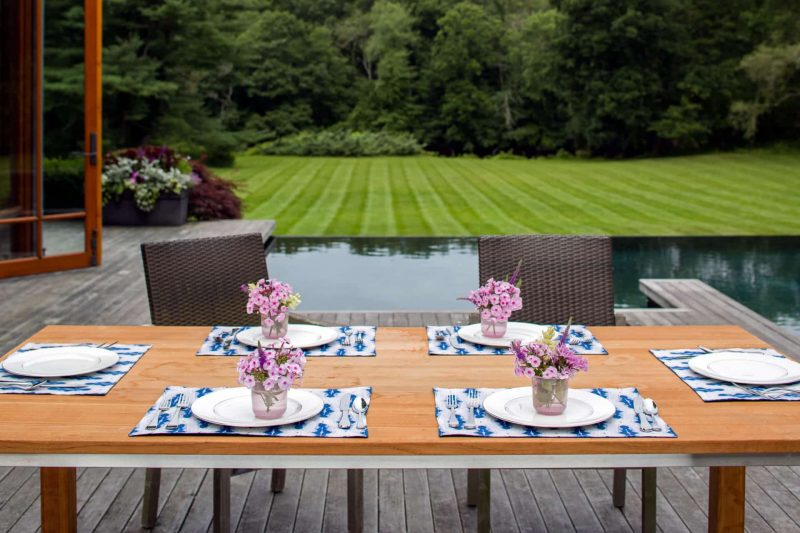 Poolside outdoor dining table setting with blue organic diamond placemats and pink flower arrangemnts