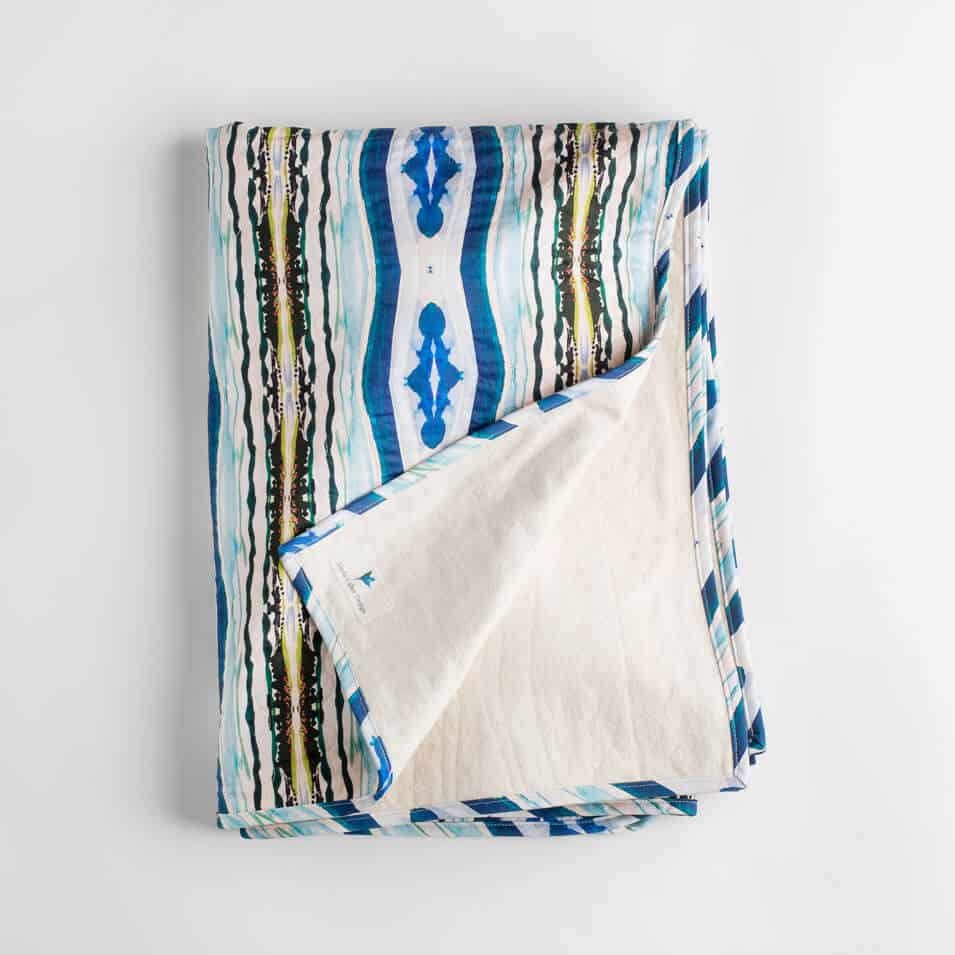 Luxury organic abstract watercolor stripe quilted coverlet with binding and flannel backing folded over