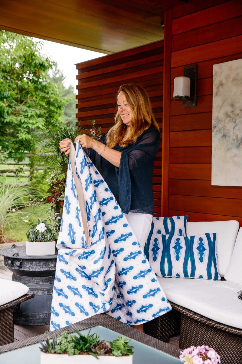Linda Cabot standing in an outdoor living room folding an organic diamond patterned quilt