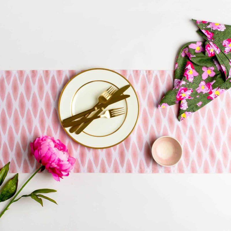 Luxury organic cinnamon diamond lattice table runner styled with gold silverware plate napkin and pink peony