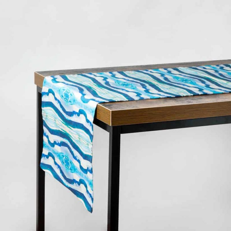 Luxury organic turquoise mirrored diamond table runner hanging off a table