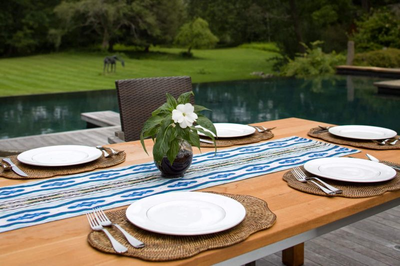 Poolside outdoor wooden dining table set with white plates wicker placemats and organic table runner