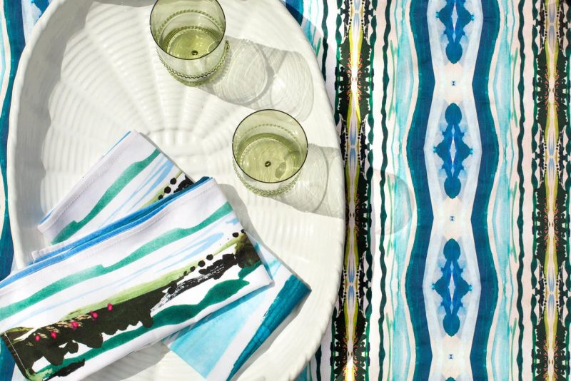 White oval platter with two green glasses and folded watercolor landscape napkins on a patterned organic tablecloth