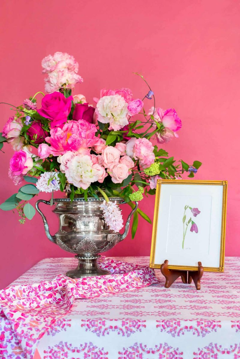 Pink floral arrangement in a silver vase next to a framed picture of pink flowers on an organic pink tablecloth in front of a pink wall