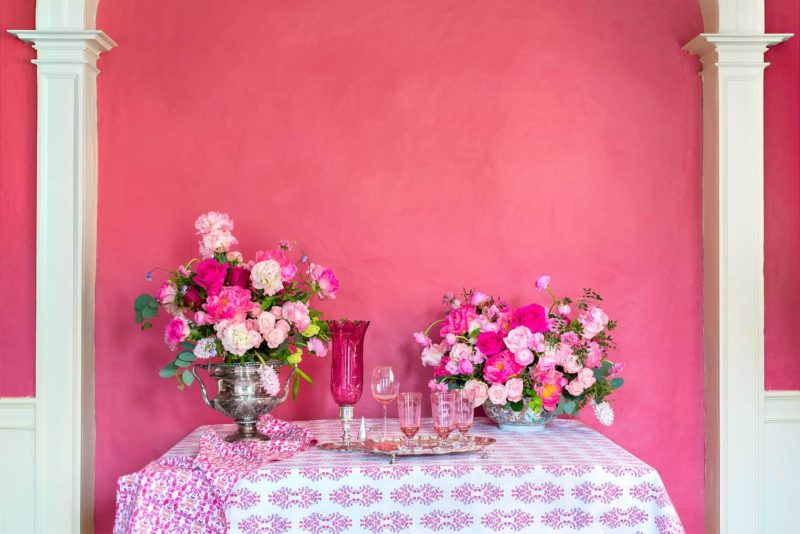 Two pink floral arrangements and a silver tray with pink glaases on a table covered with a pink organic tablecloth in a pink room with white columns