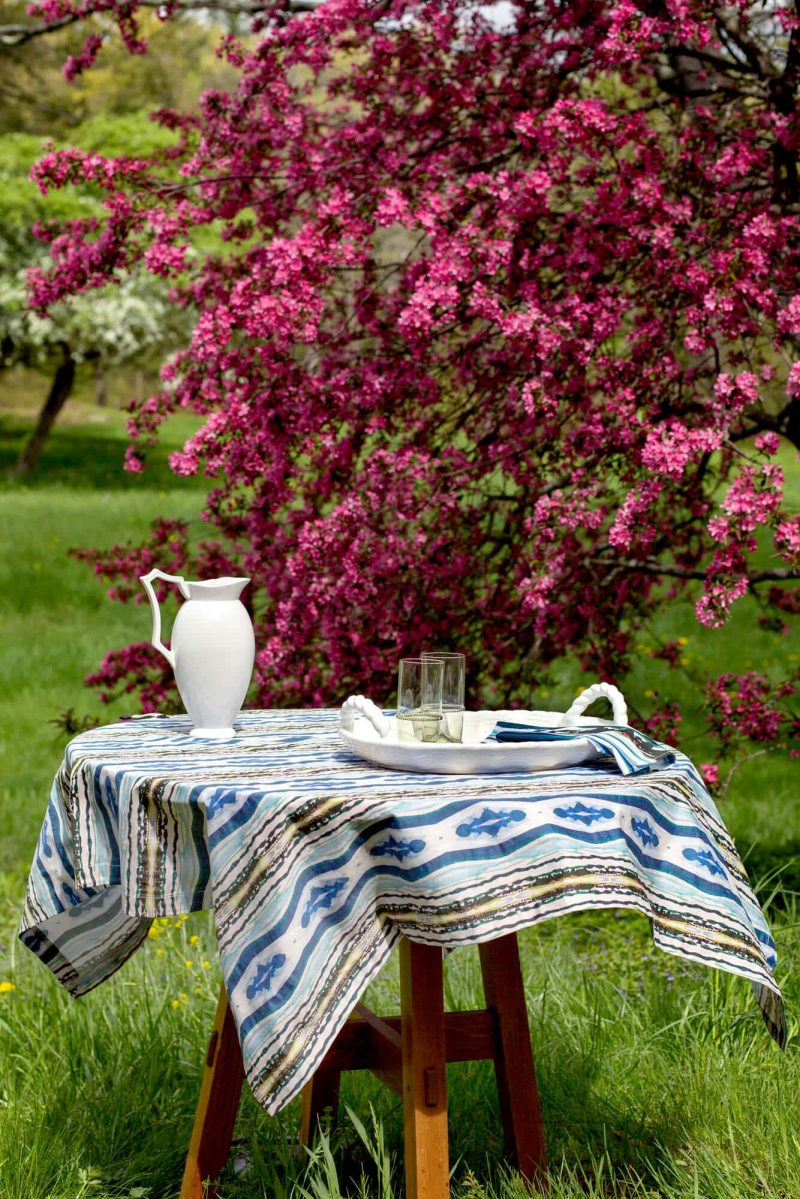 Patterned blue organic tablecloth on a table with a pitcher and glasses in a field in front of a pink flowering tree