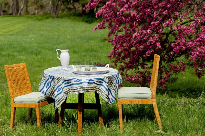 Patterned blue organic tablecloth on a table with two chairs in a field in front of a pink flowering tree