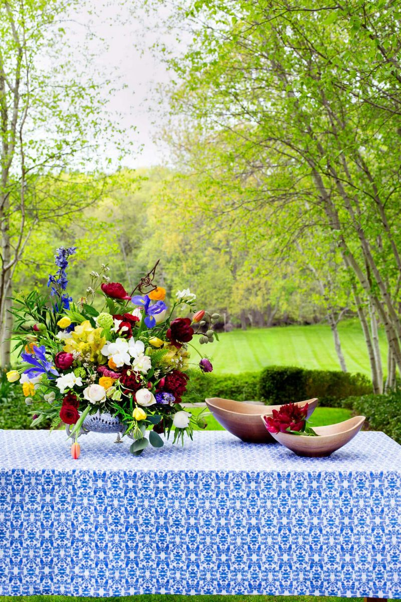 Organic blue patterned tablecloth on a table outdoors with a flower arrangement and wooden bowls