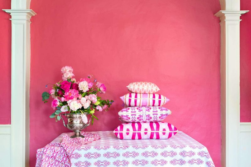 Stack of pink and orange organic pillows on a table next to a flower arrangement in front of a pink wall with white columns