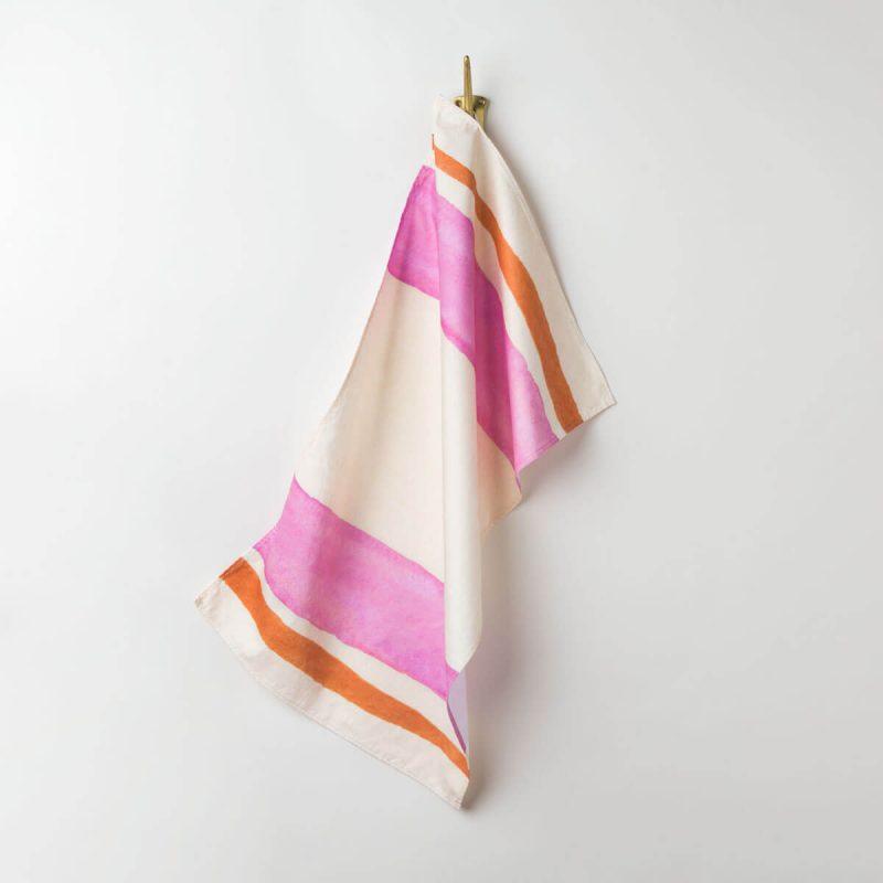 Luxury organic pink and orange watercolor stripe kitchen tea towel hanging on hook