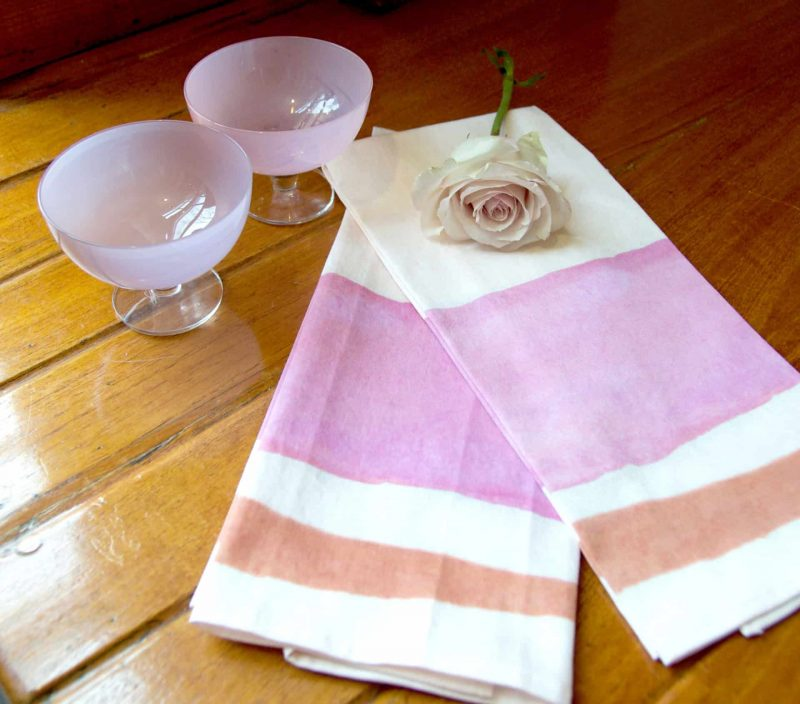 Two pink and orange watercolor striped organic tea towels with a single pale pink rose and two pink cocktail glasses