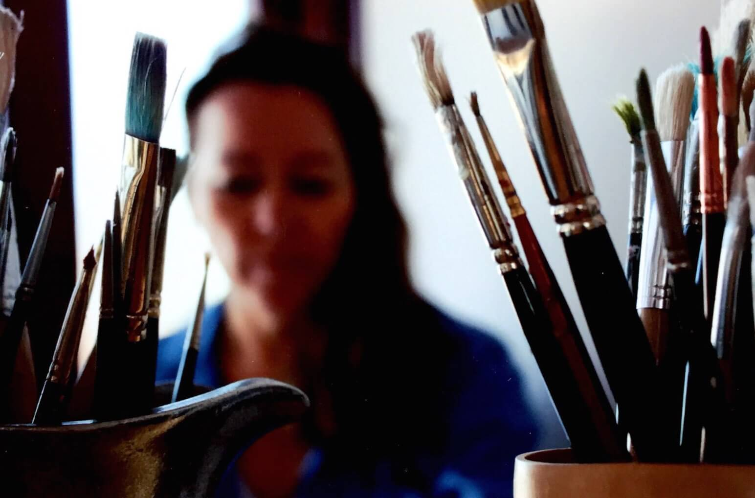 close up of cups of paintbrushes with blurred woman in background