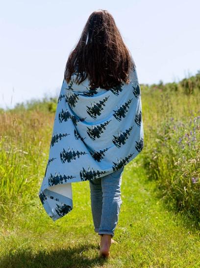 Brunette woman wrapped in a pine tree patterned blanket walking barefoot in a field